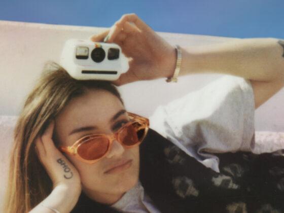 Model posiert mit einer Polaroid Go